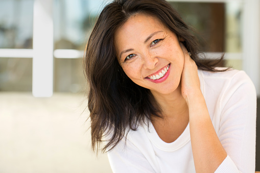 Middle Age Asian Woman Smiling from good visit to Advanced Dental Associates